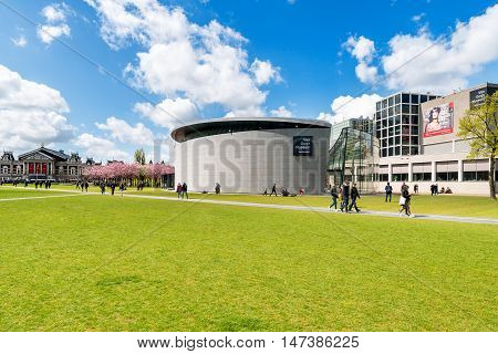 Amsterdam Netherlands on May 03 2016 : People chilling in the sun on The Museumplein in Amsterdam Netherlands at the background The Van Gogh Museum