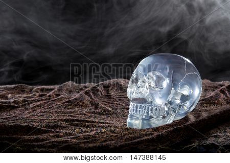Creepy crystal skull with smoke in a dark scary setting
