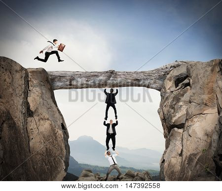 Businessmen cooperate to keep a log and pass a colleague