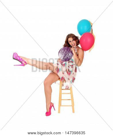 A beautiful young woman siting on a chair lifting one leg up and holding a lollypop and balloons isolated for white background.