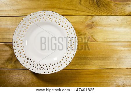 Openwork white saucer on a wooden table poster