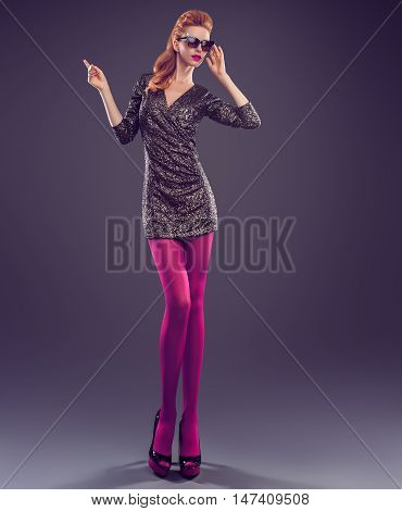 Fashion woman in Glamour Sequin black dress. Stylish Luxury Party lady. Redhead Sexy Model girl, Fashion Sunglasses, Trendy Glamour fashion Heels, Pantyhose Long Legs. Fashion Pose.Creative Outfit Dark