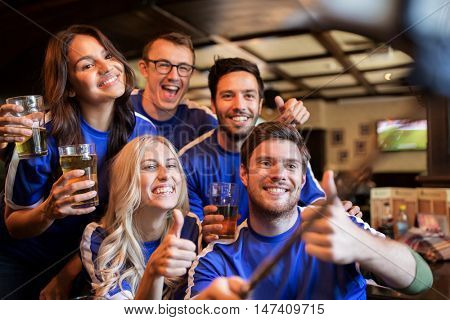 people, leisure, friendship and technology concept - happy friends or football fans taking picture by smartphone selfie stick, drinking beer and showing thumbs up at sport at bar or pub