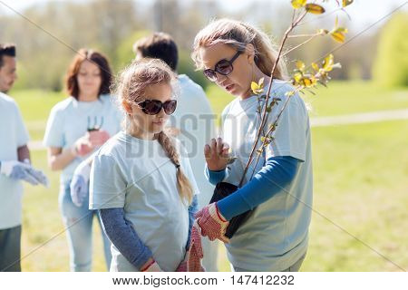 volunteering, charity, people, family and ecology concept - mother and daughter volunteer with tree seedling in park
