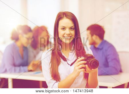 business, office and startup concept - smiling female photographer with photocamera in office with team on the back