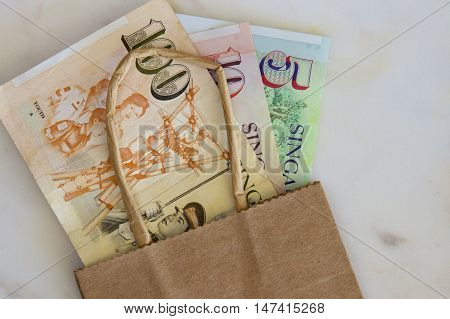 Some Singaporean dollars in a brown paper bag.