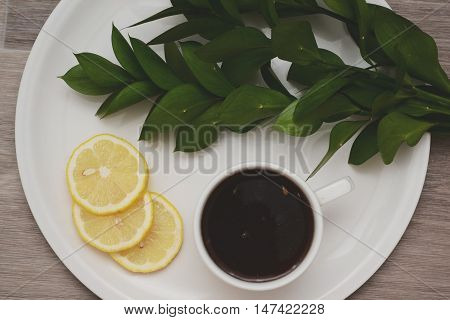 A cup of tea with lemon on the salver tray