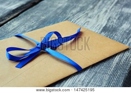 Kraft envelope tied with a blue ribbon on a wooden background. Homemade gift envelope with blue ribbon