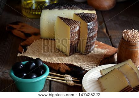 Pieces of manchego cheese cured on a wooden table accompanied by olives poster
