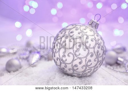 Christmas decorations silver Christmas ball with ribon in the snow on abstract background
