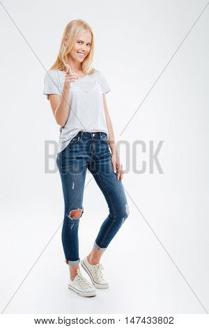 Full length portrait of a young happy woman pointing finger at camera over white background