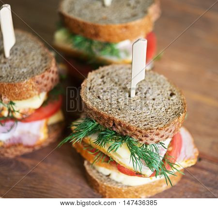 sandwiches with cheese carbonade tomato on a wooden table