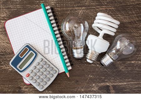 Three different light bulbs and notebook with digital calculator