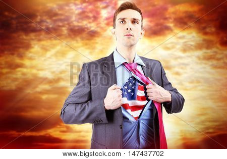 Yong businessman showing USA flag under suit on sky background.