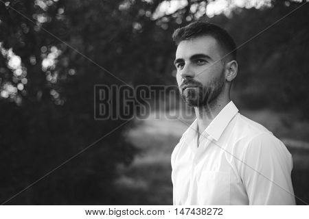 Black and white portrait of handsome casual bearded man in white t-shirt outdoors