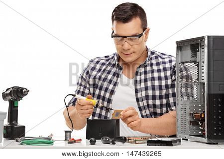 Computer technician working with a soldering iron and repairing a computer isolated on white background