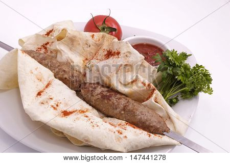 shashlik on a plate with sauce, onions and pita