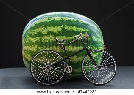 Small model of a retro vintage bicycle near a big whole watermelon
