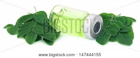Moringa leaves with extract in a vial over white background