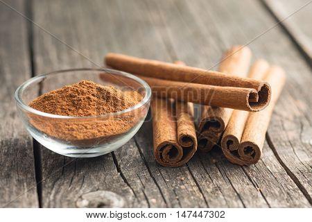 Cinnamon sticks and ground cinnamon on old wooden table.