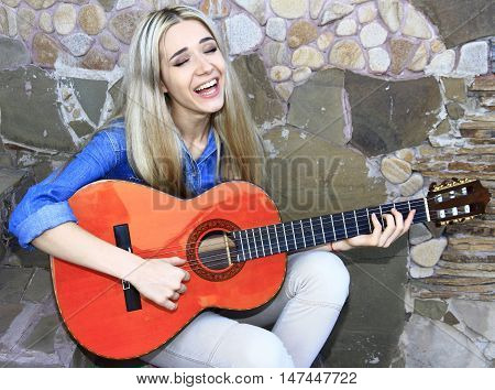 Young girl sings and plays the Spanish guitar on old wall background.