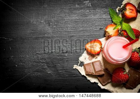 Strawberry smoothie with chocolate and mint. On a black wooden background.