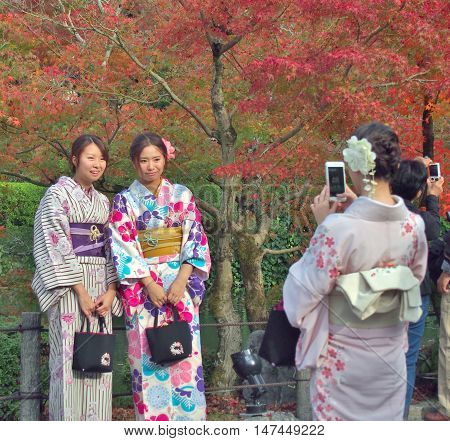 KYOTO, JAPAN - NOVEMBER 21, 2015: Two young women wear a traditional dress called Kimono are taken a photo by their friend with red leaves background at Eikan-do temple in Kyoto, Japan.