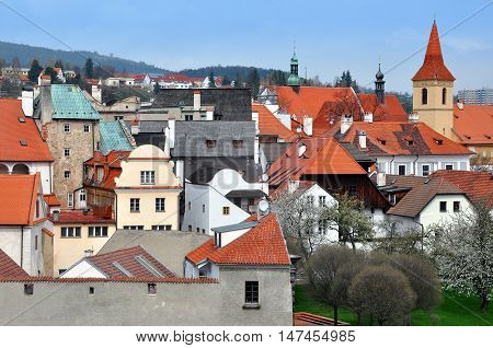 Panoramic view of Cesky Krumlov Czech Republic with landmarks. Red tiled roofs decorative gables of old houses the church the hills in perspective.