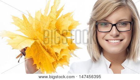 portrait of attractive  caucasian smiling woman isolated on white studio shot looking at camera wearing glasses hand holding yellow marple autumn leaves