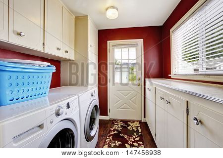 Laundry Room Interior With White Cabinets And Red Walls.