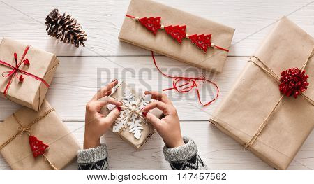 Creative hobby. Woman's hands wrap christmas holiday handmade present in craft paper with twine ribbon. Making bow at xmas gift box, decorated with snowflake on white wooden table, top view. poster