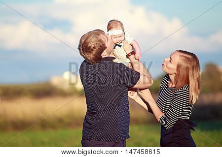 happy family playing with baby daughter outdoors. young couple showing affection to baby. the concept of happy parenthood