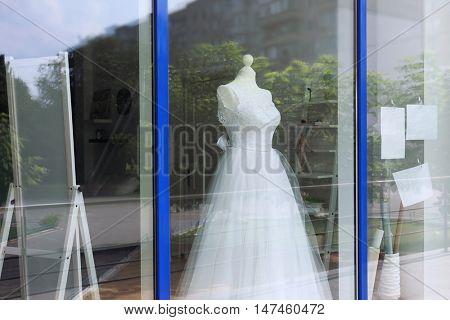 Beautiful wedding dress behind shop window