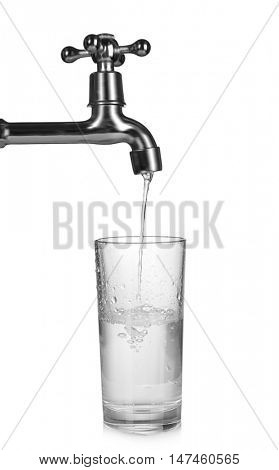 Metal tap with water dripping in glass isolated on white, saving water concept
