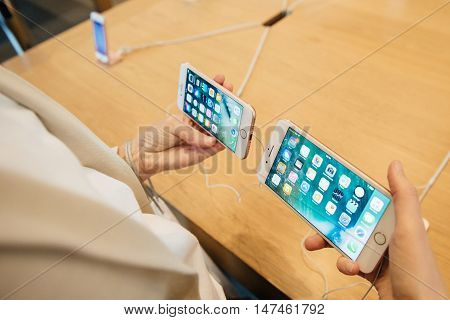 PARIS FRANCE - SEPTEMBER 16 2016: New Apple iPhone 7 being tested by woman after purchase - comparing the both iPhone 7 and iPhone 7 Plus in terms of size and specs. New Apple iPhone tends to become one of the most popular smart phones in the world in 201