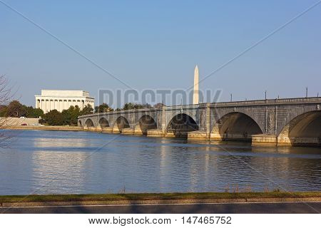 Lincoln Memorial and National Monument at sunset in Washington DC. Memorial Bridge and US capital landmarks across Potomac River.