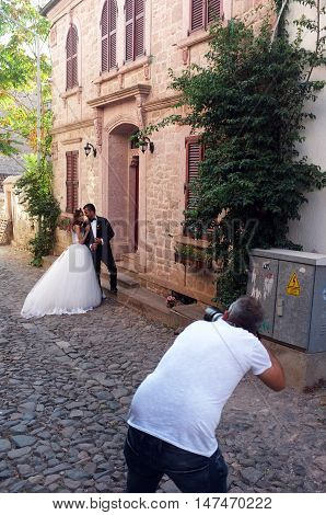 CUNDA ISLAND, TURKEY - SEPTEMBER 2nd, 2016: Married couple pose to the wedding photographer on a street in Cunda Island, Turkey
