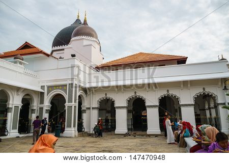 George town, Malaysia - September 2016: People in front of Kapitan Keling Mosque, George Town, Penang, Malaysia. Kapitan Keling is a mosque built in the 19th century and a popular tourist sight in George town.