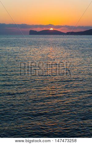 bright sun over Capo Caccia at sunset