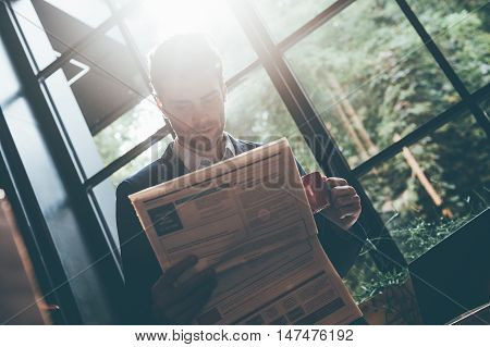 Reading the freshest news. Low angle view of confident young man reading fresh newspaper and holding coffee cup while leaning at the window sill in office or cafe