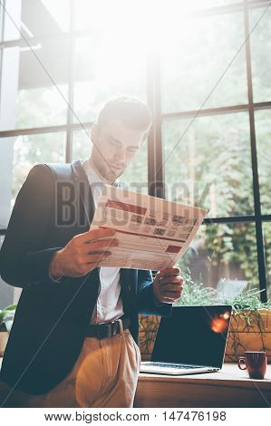 Man reading newspaper. Low angle view of confident young man reading fresh newspaper while leaning at the window sill in office or cafe