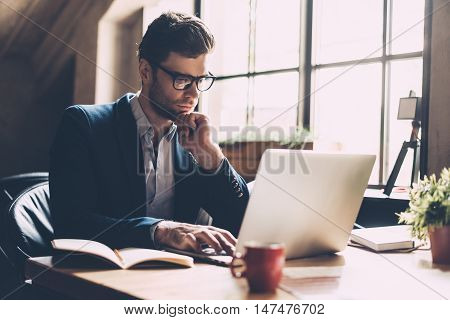 Confident businessman at work. Confident young man in smart casual wear working on laptop while sitting at his working place in office