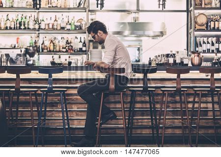Tired businessman in bar. Frustrated young man in smart casual wear sitting at the bar counter