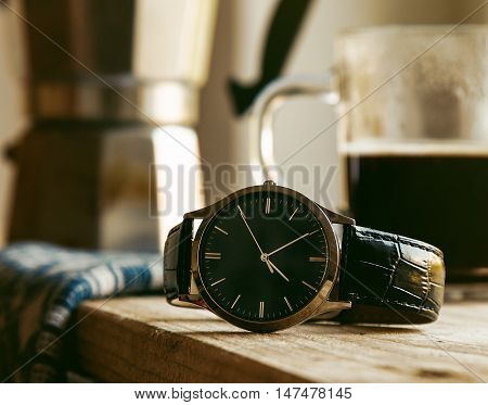 mens wrist watch on wooden table with coffe in morning light