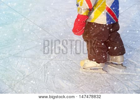 little girl learning to skate on ice in winter snow