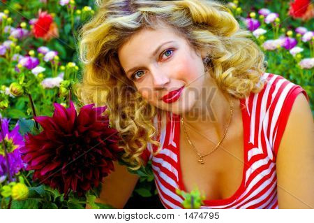 Beautiful Girl Among Dahlia Flowers
