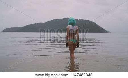 Back view of sexy beautiful woman in modern futuristic style posing in the sea. Creative look of woman wearing bikini, blue wig, black leather fingerless gloves in the water
