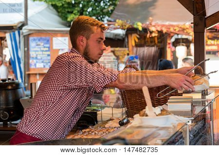 10th September 2016, Bad Dürkheim, Wurstmarkt 2016 (wine festival), Germany: An undefinite male person on the sausage market working and serving fresh cooked food