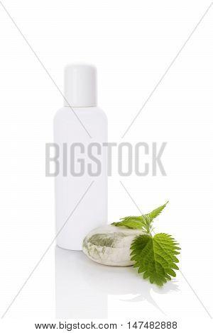 Stinging nettle cosmetics mockup. Fresh stinging nettle leaves and white plastic bottle without label isolated on white background.