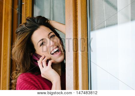 Happy Woman On Cellphone Call At Home Window
